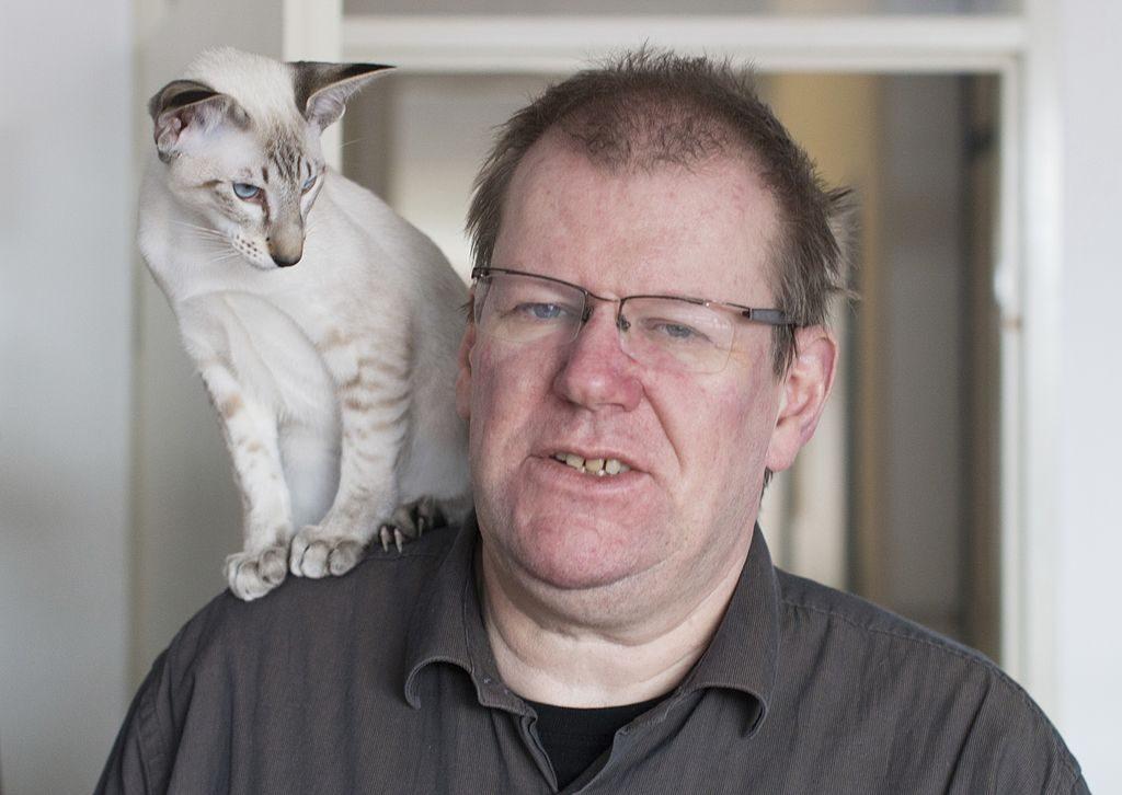 Portret Erika Zachte z kotem na prawym ramieniu