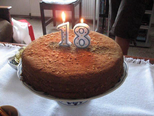 Tort urodzinowy. Zapalone świeczki w kształcie liczby 18
