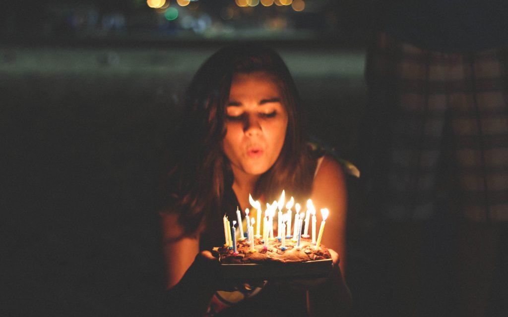 Dziewczyna zdmuchuje świeczki na torcie urodzinowym