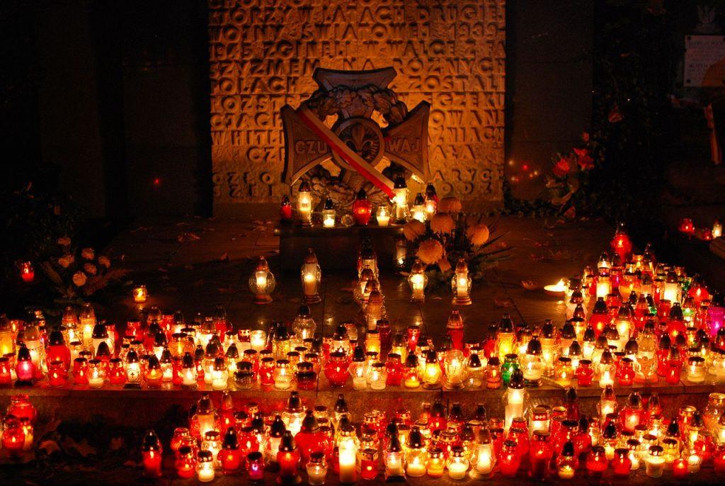 Oświetlony zniczami grób harcerski w Łodzi. Na drugim planie napis Czuwaj i lilia harcerska, przepasane biało-czerwoną szarfą. Za nimi ściana pamiątkowa.