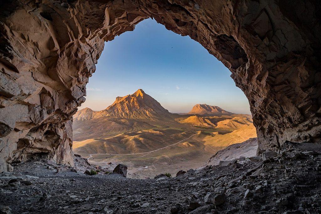 Widok z wnętrza jaskini na góry i ciągnącą się drogę.