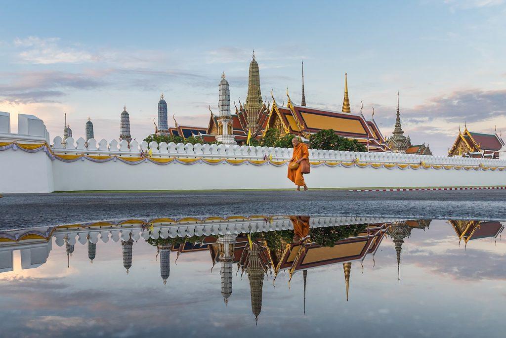 Mnich buddyjski w pomarańczowej szacie przechodzi koło muru oddzielającego go od buddyjskiej świątyni. On, świątynia i niebo odbijają się w kałuży