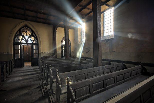 Wnętrze starego kościoła w trakcie dnia. Widok na tył kościoła i okna.