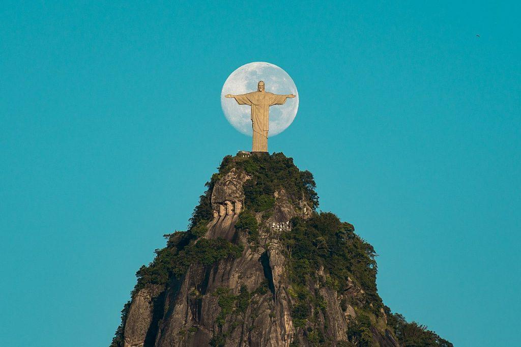 Widok statuy Chrystusa odkupiciela na szczycie góry, z księżycem w tle